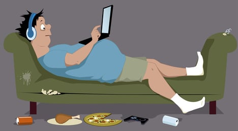 Overweight guy lying on a couch with a laptop
